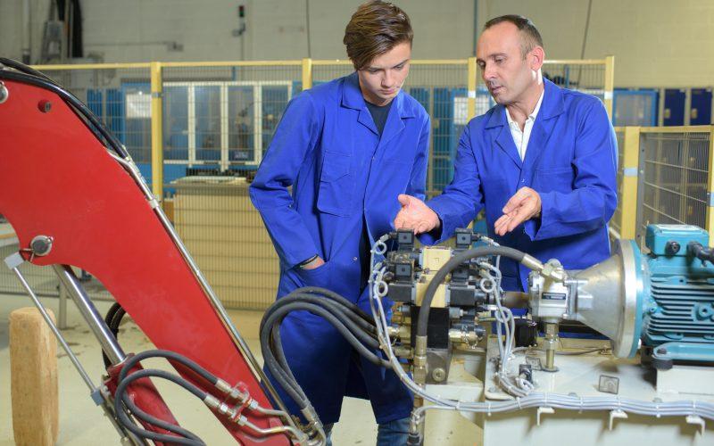 Engineers looking at hydraulic arm mechanism